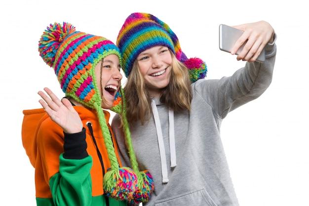 Зимний портрет двух счастливых красивых девушек-подростков Premium Фотографии