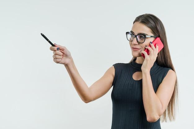 Деловая женщина в очках с телефоном указывает с ручкой Premium Фотографии