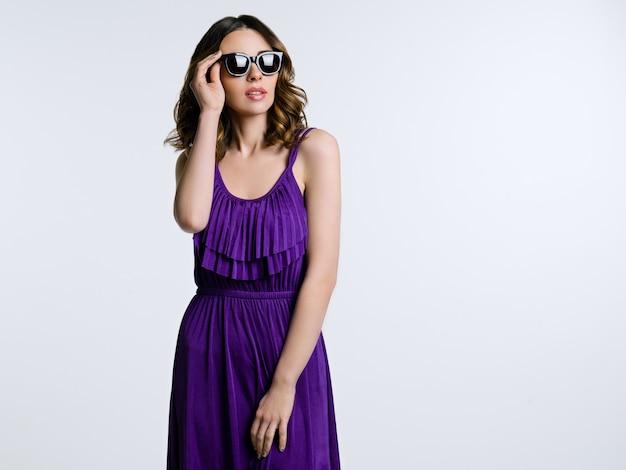 サングラスと紫色のドレスの美しいブルネット Premium写真