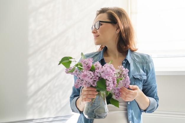 ライラックの花束と自宅で美しい成熟した女性の肖像画 Premium写真