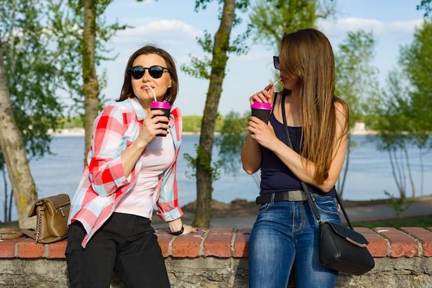 コーヒーを飲みながら幸せな二人の女友達 Premium写真