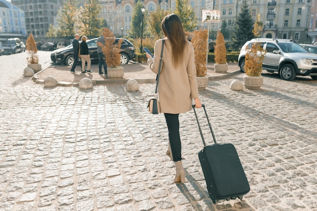 旅行スーツケースと街を歩いている若い美しい女性 Premium写真