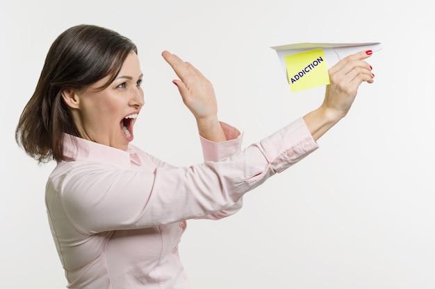 中年の女性は言葉中毒と紙飛行機を出してください。 Premium写真