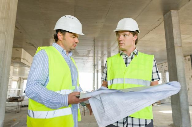 男性の建設労働者と建設現場のエンジニア Premium写真