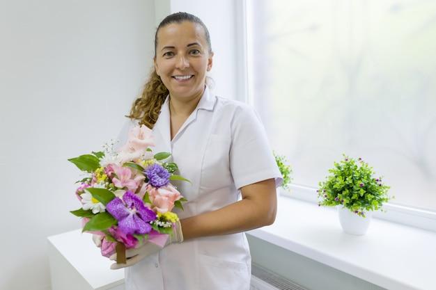 花の花束を持つ女性看護師 Premium写真