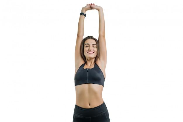 若い女性は、目を閉じて、白で隔離され、黒のスポーツウェアでスポーツを楽しんでいます Premium写真