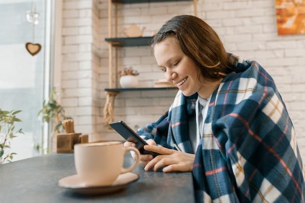 Осенний зимний портрет улыбающейся девочки-подростка с мобильным телефоном в кафе Premium Фотографии