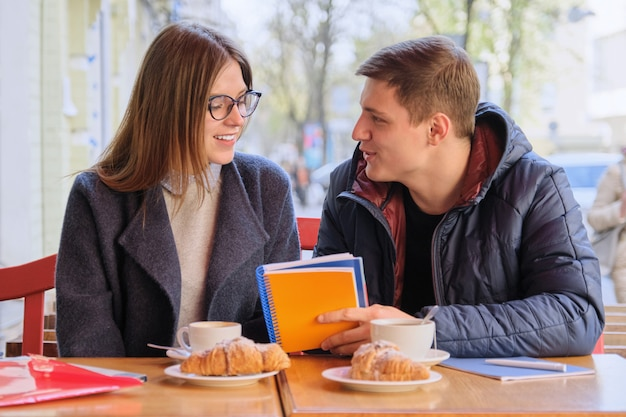 若いカップルの学生が屋外カフェで勉強します Premium写真