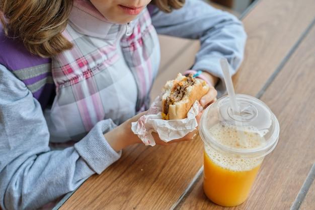 Крупным планом руки ребенка есть гамбургер и пить апельсиновый сок Premium Фотографии
