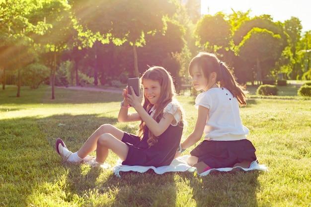 陽気な小さなガールフレンドは、スマートフォンで遊ぶ Premium写真