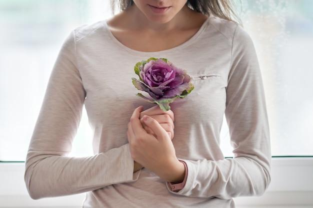Молодая красивая женщина с фиолетовым цветочным цветком капусты Premium Фотографии
