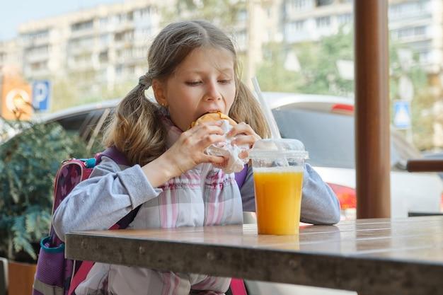 オレンジジュースとハンバーガーを食べるバックパックで女子生徒 Premium写真