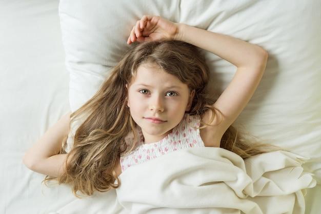 枕の上の長いウェーブのかかった髪と金髪の子供女の子 Premium写真