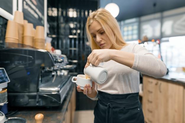 ミルクを保持している若いバリスタがコーヒーのカップを準備します Premium写真