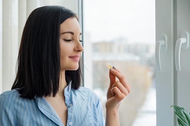 Молодая женщина, стоя у окна, принимая витамин Premium Фотографии