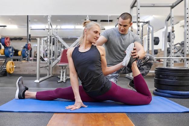 若い運動女性のストレッチを助ける若い筋肉の強い男 Premium写真