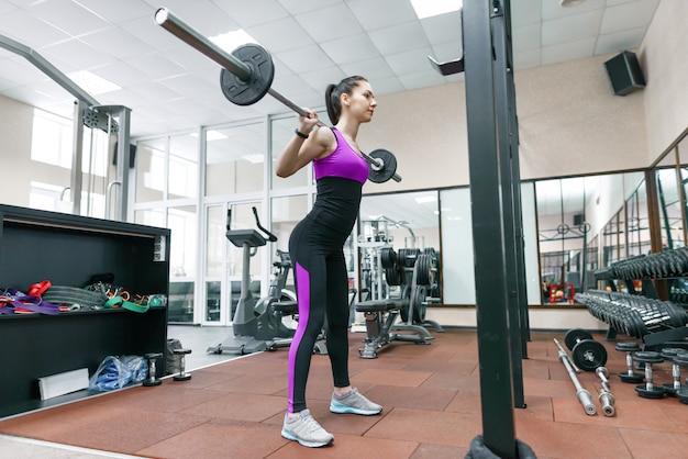 現代のスポーツジムのマシンで運動若い運動女性 Premium写真