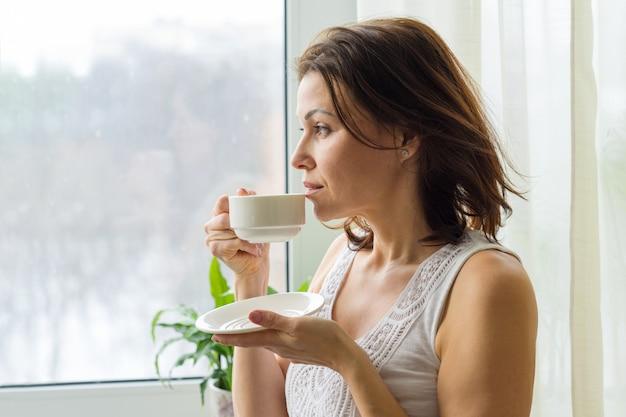 熟女は朝のコーヒーを飲む Premium写真