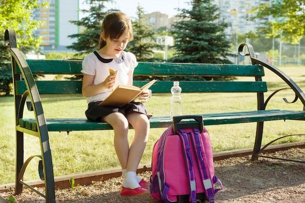 アイスクリームを食べる女子高生読書の肖像画 Premium写真