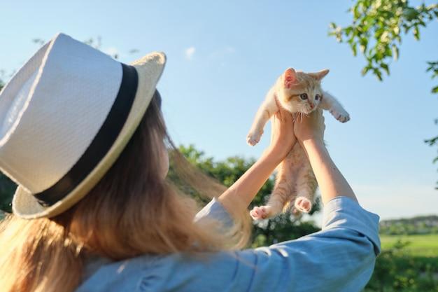 Молодая девушка держит маленький рыжий котенок в саду Premium Фотографии