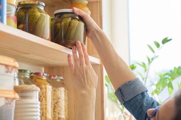Продукты питания на кухне, женщина берет банку соленых огурцов Premium Фотографии
