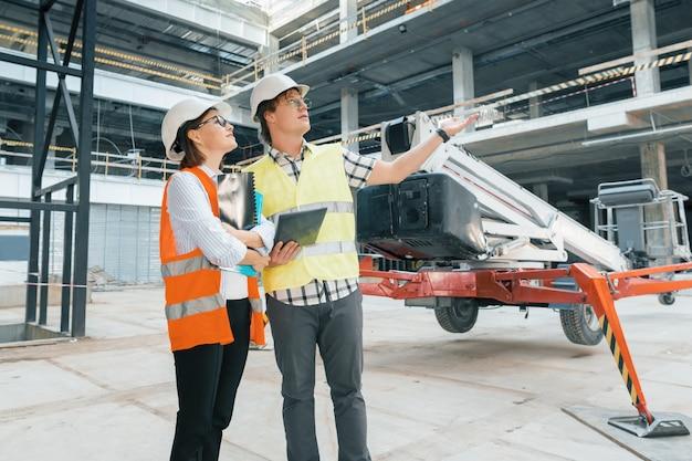 女性エンジニアと建設現場で男性ビルダー Premium写真