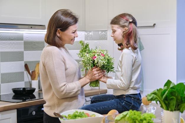 День матери, дочка ребенка дарит маме букет весенних цветов Premium Фотографии