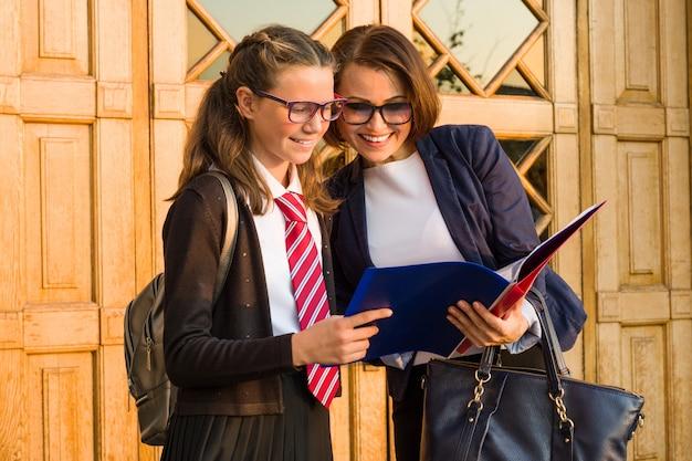 高校の先生が女子学生と話しています。 Premium写真