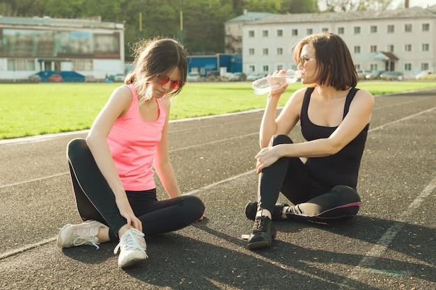 トレーニングの後休んでいる母と娘のティーンエイジャー Premium写真
