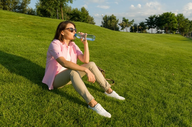 Взрослая женщина пьет воду из бутылки Premium Фотографии