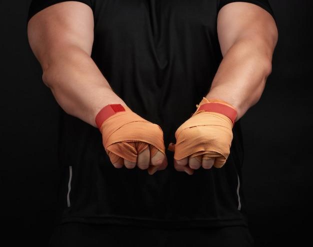 Взрослый мужчина в черной форме и мускулистом теле стоит в спортивной позе Premium Фотографии