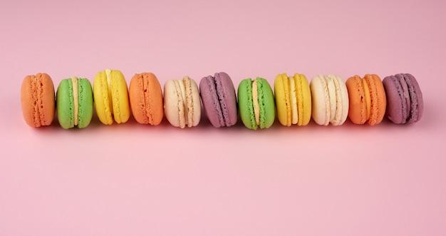 Множество разноцветных круглых печеных макаронных пирожных на светло-розовом фоне Premium Фотографии