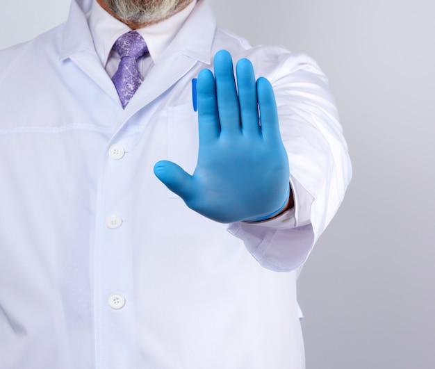 Мужской доктор в белом халате и синих стерильных перчатках показывает жест остановки правой рукой Premium Фотографии