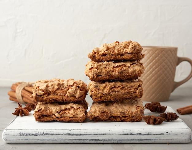 木の板とブラックコーヒーと白いセラミックカップに焼きたてのクラクフのメレンゲクッキーのスタック Premium写真
