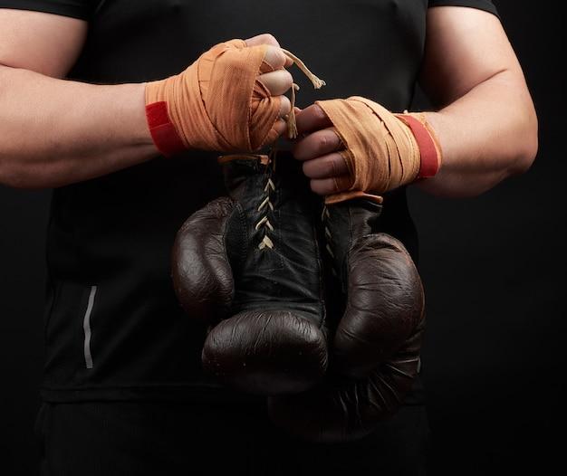 黒の制服を着た選手が手に非常に古い茶色のボクシンググローブを保持 Premium写真