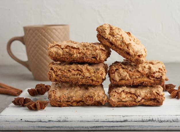 木の板とセラミックカップに焼きたてのクラクフのメレンゲクッキー Premium写真