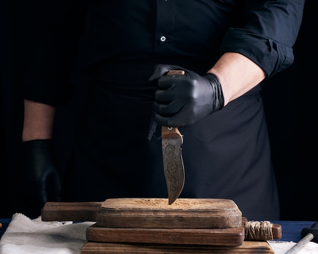 Шеф-повар в черной рубашке и черных латексных перчатках держит винтажный кухонный нож Premium Фотографии