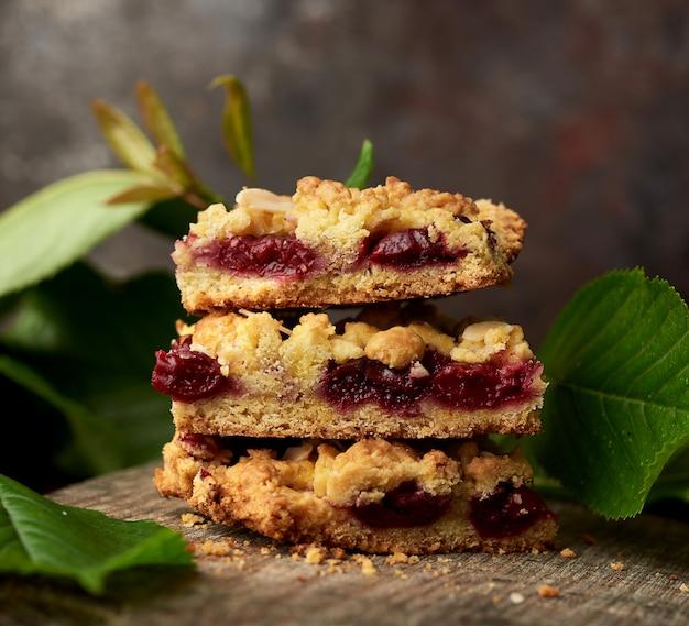 Стек квадратных кусков рассыпчатого пирога с вишней на деревянной доске Premium Фотографии