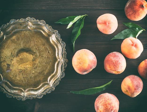 木製の茶色の背景に熟した桃 Premium写真