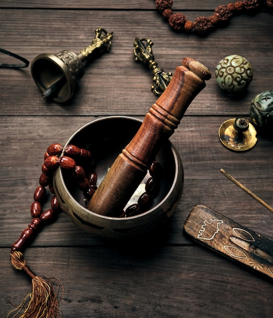 銅歌ボウルと茶色のテーブルの上の木の棒 Premium写真