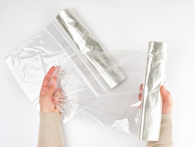 女性の手でオーブンで製品を焼くためのプラスチックフードラップ Premium写真