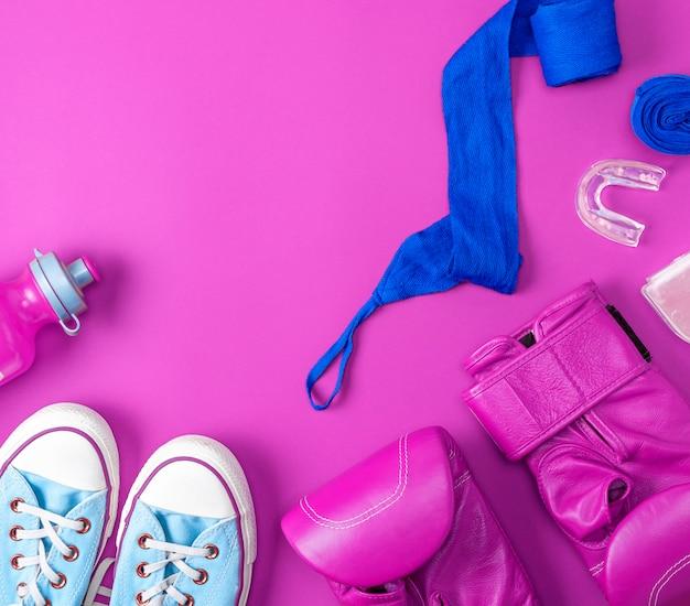 Пара кожаных розовых боксерских перчаток, синяя текстильная повязка и бутылка с водой Premium Фотографии