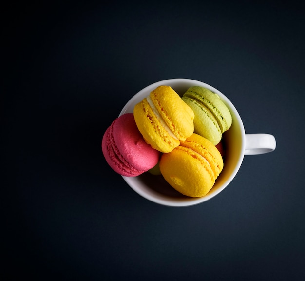 白いセラミックカップにアーモンドの小麦粉マカロンのケーキ Premium写真