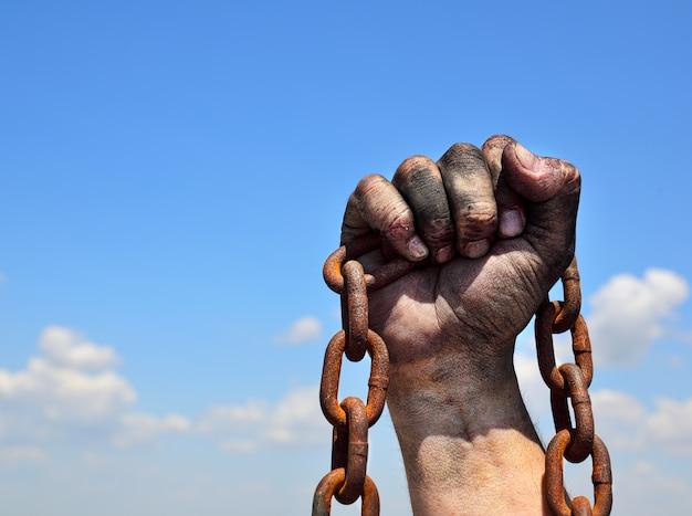 人間の男性の右手でさびた鉄鎖 Premium写真