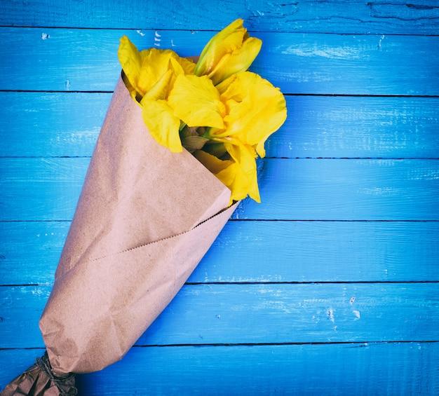茶色のクラフト紙に包まれた黄色いアイリス Premium写真