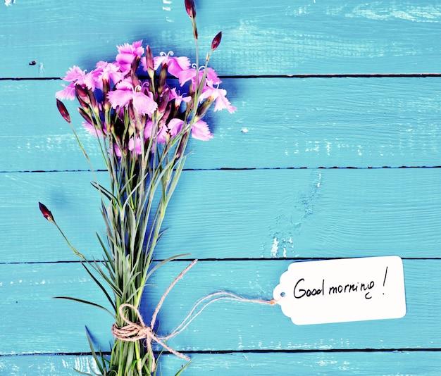 ピンクのカーネーションと紙タグの花束 Premium写真