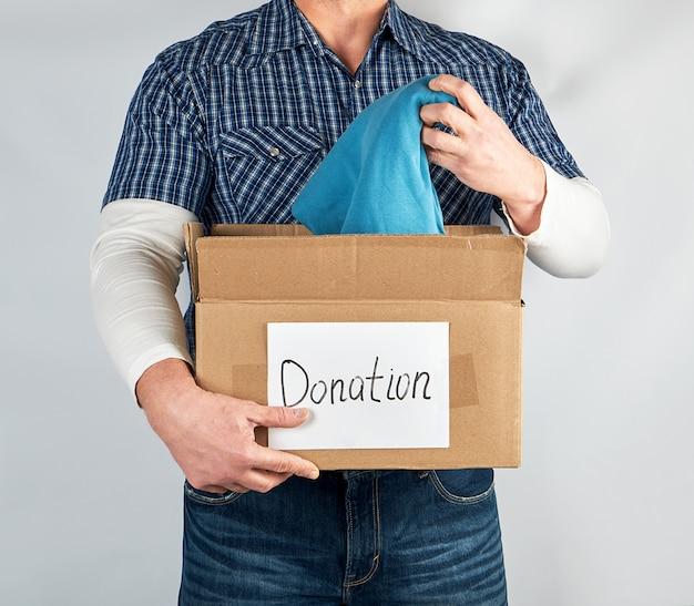 青い市松模様のシャツとジーンズの男は大きな茶色の紙箱を保持します Premium写真
