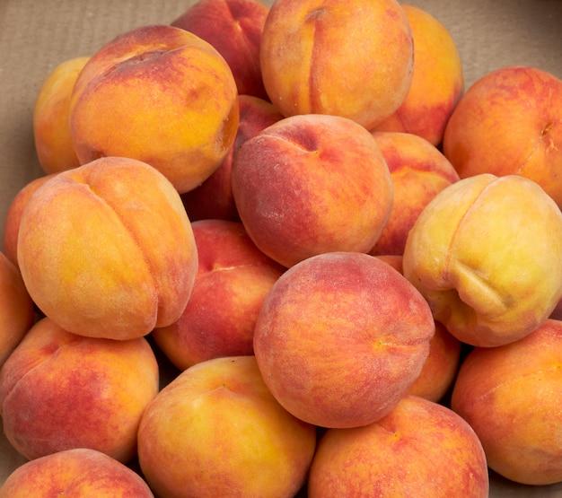 Куча спелых желто-красных круглых персиков Premium Фотографии
