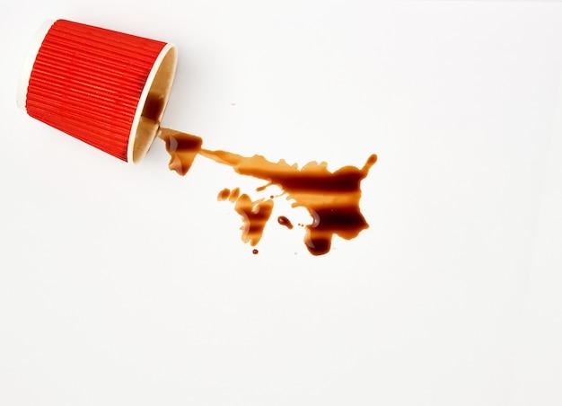 赤い紙コップからこぼれたブラックコーヒー Premium写真