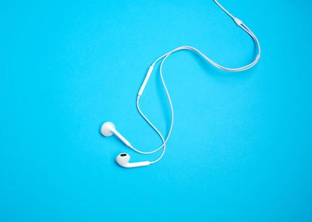 Белые наушники с кабелем на синем фоне Premium Фотографии